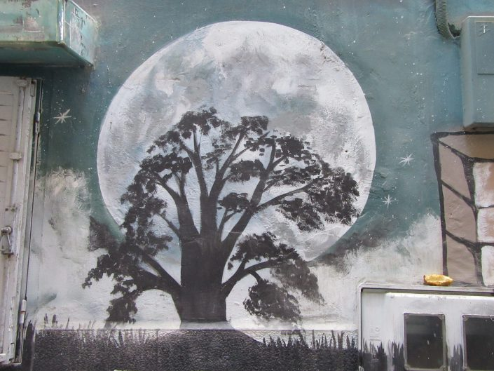 Street art paining of a black tree in the background of full moon