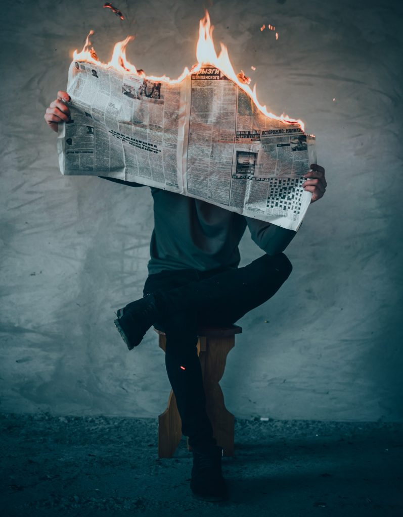 man sitting reading burning newspaper to illustrate microdosing and emotions
