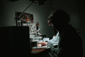 Person sitting in the dark, doing some focused work, writing