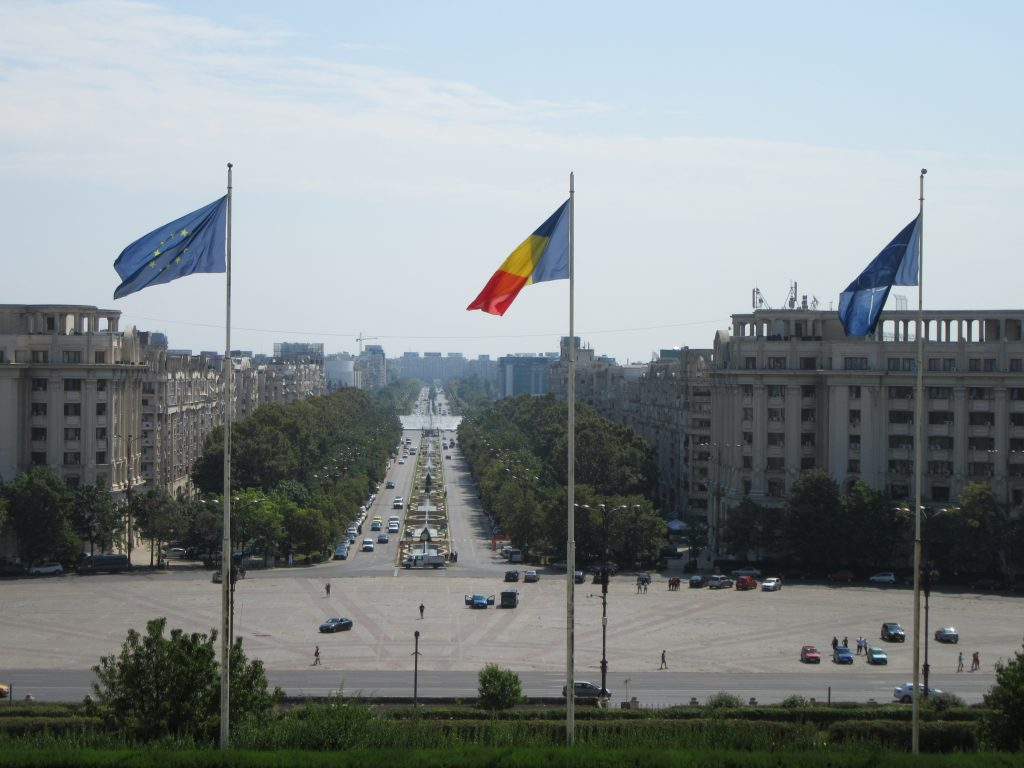 View throughn the main Balcony of Bucharest Parliament Palace. Three flags visible: EU, Romania's, Nato