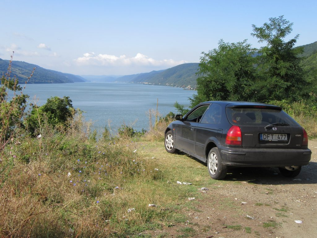 Road Trip to Romania. Scenic Southern Romania Road 57 Danube and Serbian Border in the middle of the river and Honda Civic