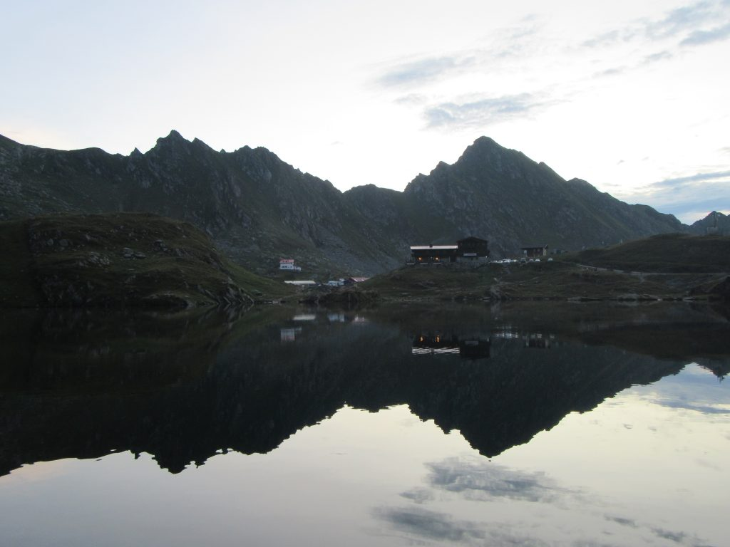 Balea Lake and Reflection of Mountain Hut and Mountains in the calm evening